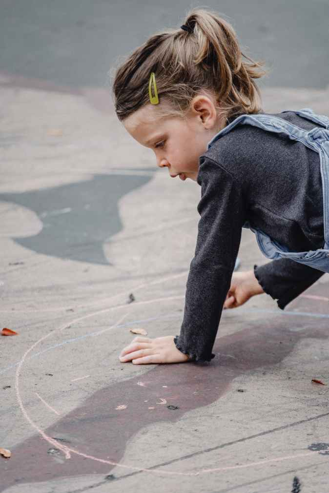 little girl drawing circle with chalk